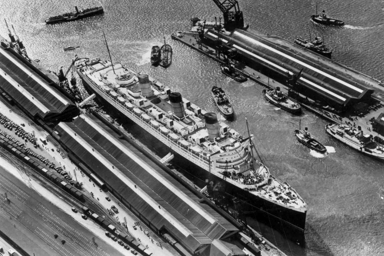 Old black and white photo of Queen Mary in port
